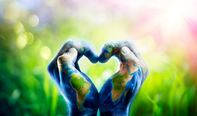 Wall Mural - Human Hands Shaping A Heart Patterned With A World Map - images furnished by NASA
