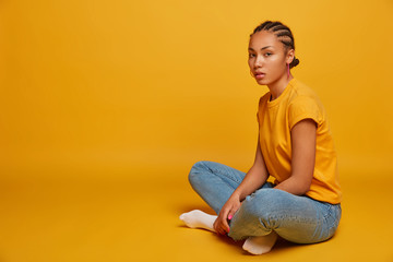 Photo of attractive young female model with cornrow braid hairstyle sits in lotus pose, feels relaxed, wears casual t shirt and jeans, isolated on yellow background, copy space for your advertisement.