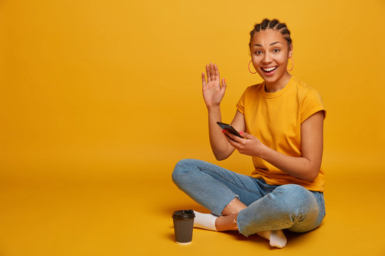 Optimistic glad Afro American girl uses mobile phone for recording blog, sits relaxed crossed legs on floor, waves palm and greets someone, drinks caffeine beverage, uses modern technologies