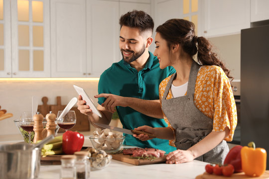 Lovely young couple with tablet cooking together in kitchen