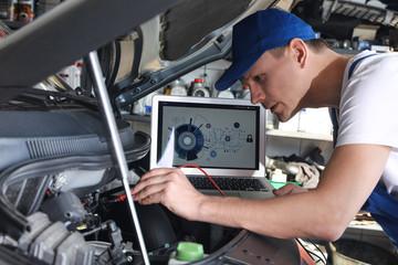Mechanic with laptop doing car diagnostic at automobile repair shop