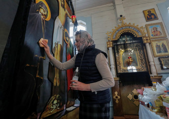 Woman disinfects and cleans an icon during a service in an Orthodox Church in Dyatlovo