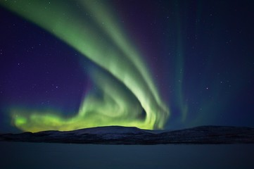 dancing green northern lights in the night sky over a mountain range in lapland finland