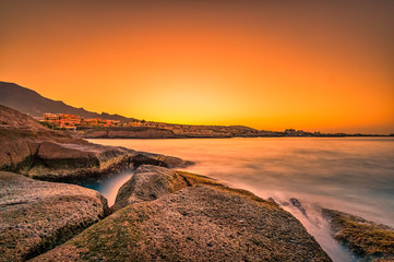 Warm colors at an impressive sunrise on stones nearby the sea.