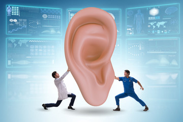 Doctor examining giant ear in medical concept