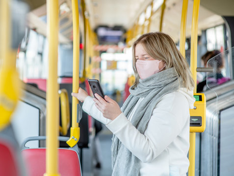 Youn woman wearing protective mask against virus and air pollution in the bus holding on to the handrail and using a smartphone