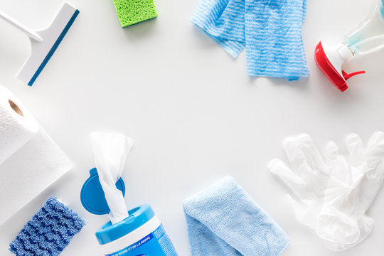 A top down view of a variety of household cleaning supplies against a white background and copy space in the middle.