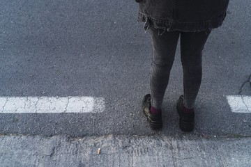 High angle shot of a person in a black outfit standing on the sidewalk