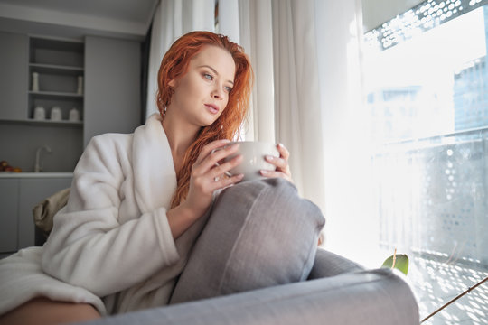 stayhome concept,  attractivewoman sitting in bed , holding cup of black coffee, enjoying peaceful calm weekend vacation morning time alone in bedroom at home or hotel.