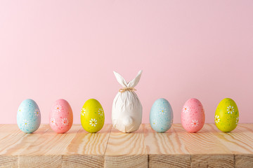 Easter egg wrapped in a paper in the shape of a bunny with colorful Easter eggs. Minimal Easter background. Spring holidays concept.