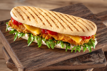 panini sandwich with crispy chicken and rucola salad
