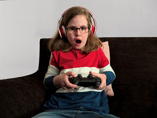 Amazed girl with headphones playing video game console