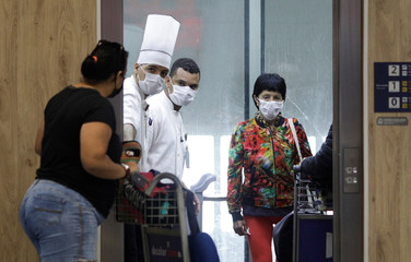 Passengers and workers wearing protective masks are pictured inside an elevator at Galeao international airport during the coronavirus disease (COVID-19) outbreak in Rio de Janeiro