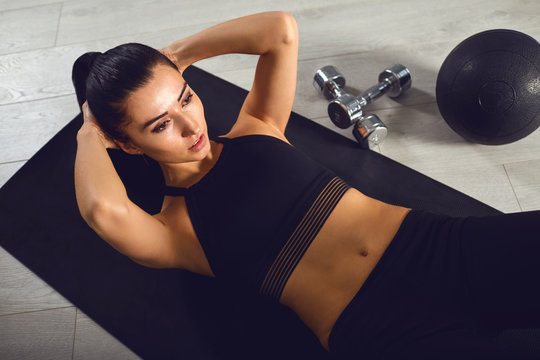 Exercises abs. Sporty girl in black sportswear doing abc exercises indoors.