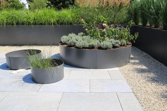 Moderne Garten- und Terrassengestaltung im Materialmix:Terrassen aus Steinplatten und Schotter sowie Metall Pflanzgefäße mit Gräsern und und blühenden Kübel Pflanzen