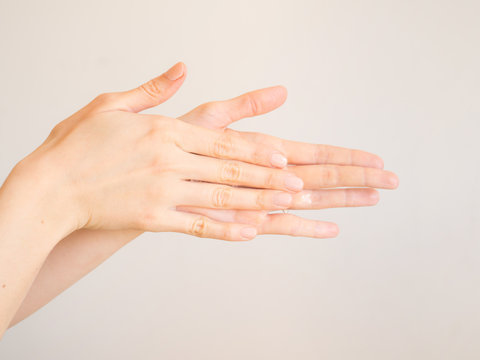 Female hands cleaning washing with sanitizer gel over bright gray background