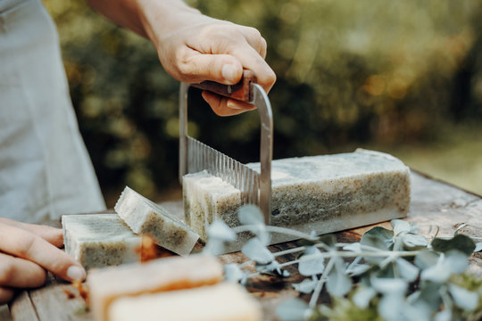 Woman is making handmade natural soaps on an old wooden table