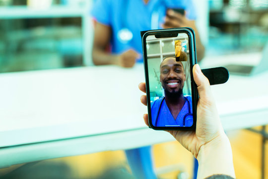 Portrait of a sick patient coughing into tissue being helped via tele medicine by a male doctor wearing blue scrubs uniform using smartphone mobile phone