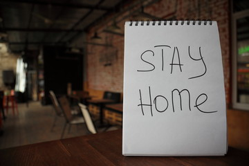 Stay home appeal written by hand on a paper on the empty street cafe table