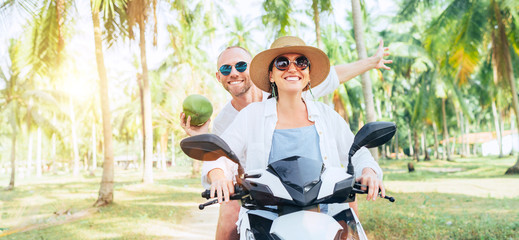Happy smiling couple travelers riding motorbike scooter under palm trees. Laughing man carrying a...