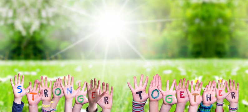 Children Hands Building Colorful Word Stronger Together. Green Grass Meadow As Background