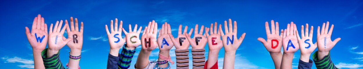 Children Hands Building Colorful German Word Wir Schaffen Das Means We Can Do It. Blue Sky As Background Wall mural