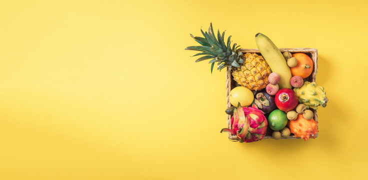 Rattan box full of exotic thailand fruits - pineapple, pitahaya, kiwano, african horned melon, tamarillo fruit, granadilla, feijoa, salak, snake fruits, maracuya, rambutan, lychee, longan, tamarind