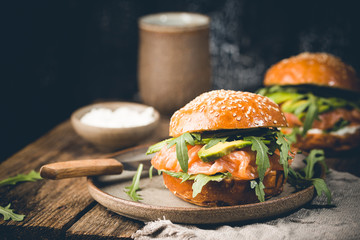 Burger sandwich with salmon, cream cheese, avocado and arugula on a light background, concept diet food, sandwich take away, healthy fast food