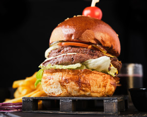 Double beef cheeseburger with american french fries on a dark background.