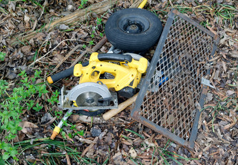 Discarded power saw, tire and metal grate in alley.