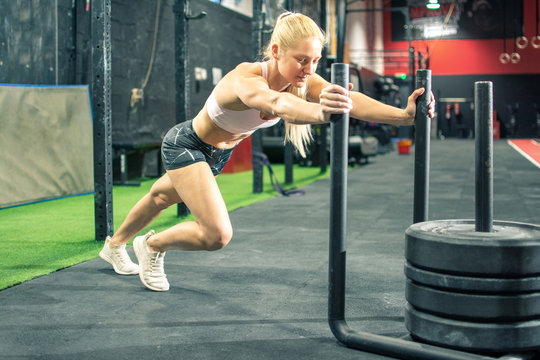 Fit young woman pushing the weight sled at gym