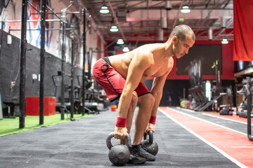 Young sportsman doing squats with kettle bells at gym.