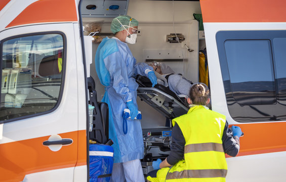 Alert pandemic Covid-19. Doctors with protective masks assist a man with Corona Virus lying on a stretcher inside an emergency ambulance. Global warning alert. Transportation logistics for emergency
