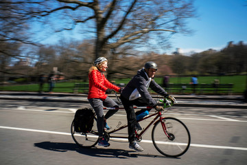 People ride a bicycle as they enjoy the day at Central Park while the coronavirus disease (COVID-19) outbreak continues in New York