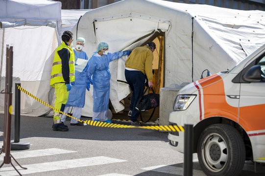 Alert pandemic Covid-19. Triage hospital field tent for the first AID, a mobile medical unit for patient infected with Corona Virus. Doctors with protective masks check the patiences at the entrance.