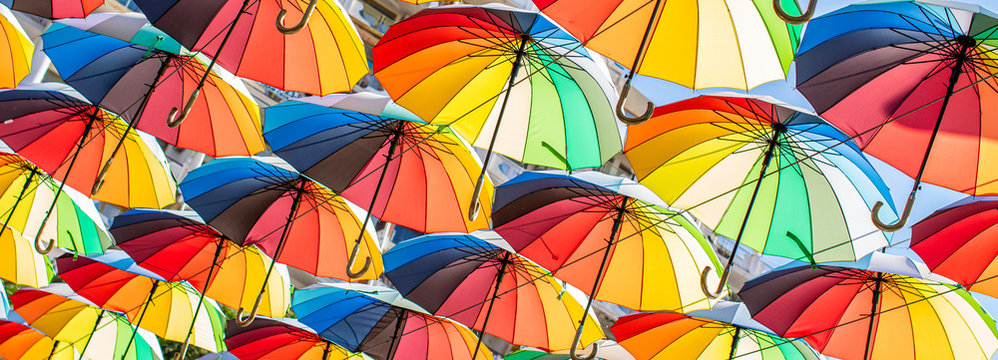 Colorful umbrellas Blue, green, red, rainbow umbrellas background Street with umbrellasin the sky Street decoration.