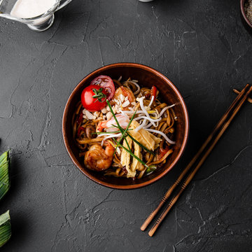 Chinese dishes in a clay plate on a black concrete background with ingredients for delivery