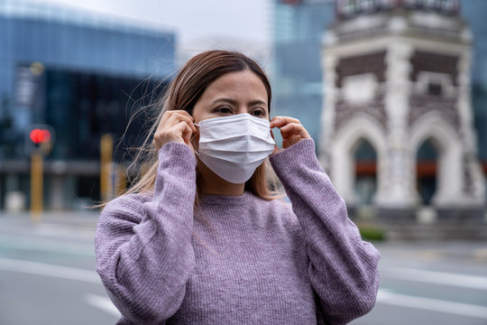 A beautiful middle aged Asian woman wearing a medical mask to protect from infection of virus, pandemic, outbreak and epidemic of disease in Christchurch city, New Zealand. Social distancing.