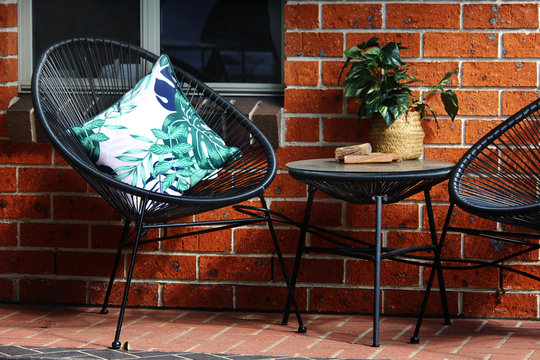 Front verandah of a new red brick house with black Acapulco chair and coffee table setting and pot plant.