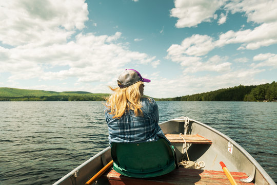 Woman on a Aluminum Rustic Boat in Maine on a Summer Day with Blonde Hair Blowing and Mountains in Background
