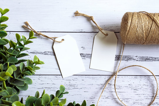 Two blank gift tags on a wooden background with twine and eucalyptus leaves - gift tag mockup for weddings, birthday, thank you, your own designs