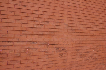 Vintage burnt orange color brick wall background with grungy texture (angle view)