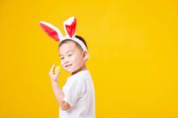 little children boy smile standing so happy bunny ears in Easter festival day holding easter eggs