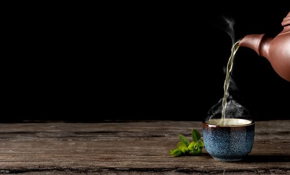 Hot green tea is poured from the teapot into the blue bowl, vintage wooden table, steam rises above the cup. Tea leaves next to the cup. Close-up, tea ceremony, minimalism, copy space for text.