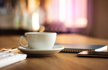 Closeup white cup of coffee with smartphone, notebook and computer keyboard on table in cafe. Vintage light, blurred and bokeh background