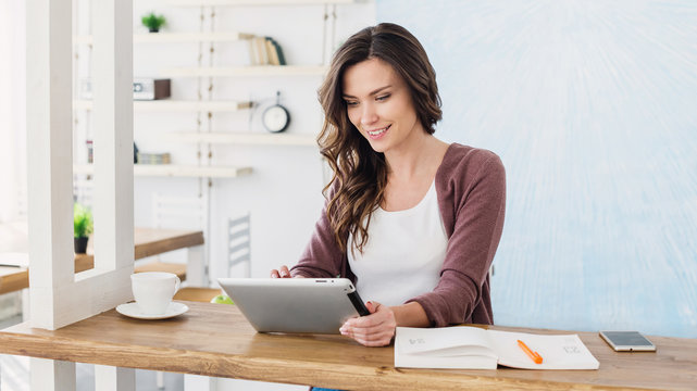 Young beautiful woman using digital tablet at home, Cheerful smiling girl sitting at her workplace, Technology, business, home work, online learning, studying concept, Distance education