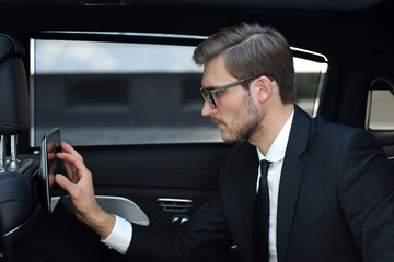 Thoughtful young businessman sitting in the luxe car and using his tablet.