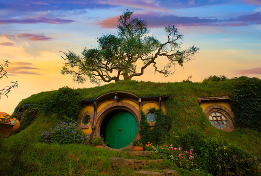 """MATAMATA- NEW ZEALAND -APRIL -19- 2019 : Hobbiton - movie set created for filming the Lord of the Rings and """"Hobbit"""" movies - Matamata, New Zealand,evening scene with twilight sky image"""