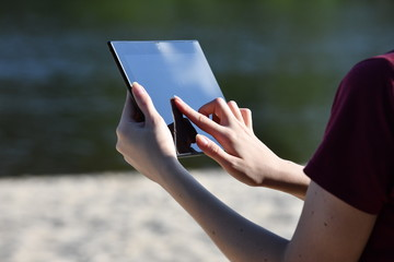 Female hands with a black graphic tablet
