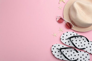 Flat lay composition with flip flops and beach accessories on pink background. Space for text